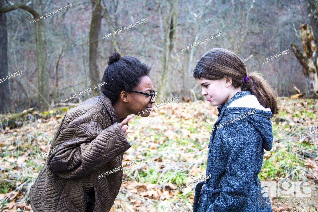 Stock Photo: Two teens/ Pre-teens arguing. One African American teen girl, yelling and correcting her caucasian friend/sister. She is bossing her around.