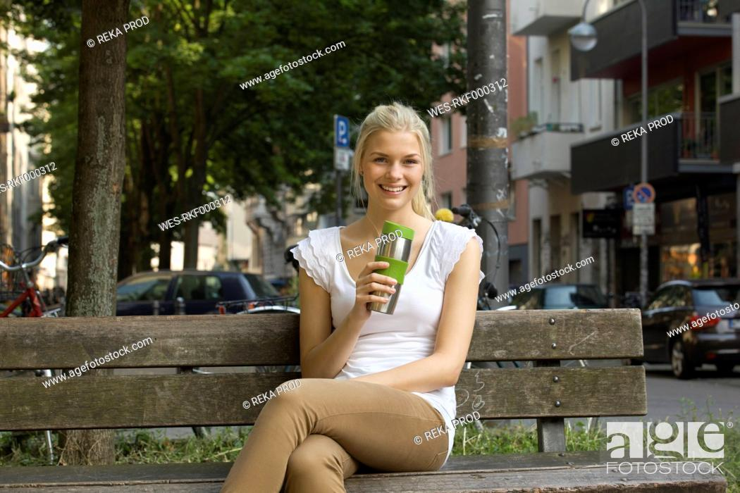 Stock Photo: Germany, North Rhine Westphalia, Cologne, Young woman sitting on bench with coffee cup, smiling, portrait.