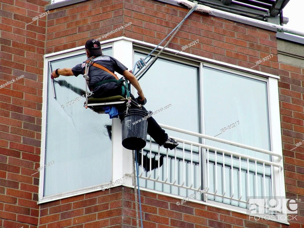 Stock Photo: USA, United States of America : Window cleaner, abseiling from the roof to each floor.
