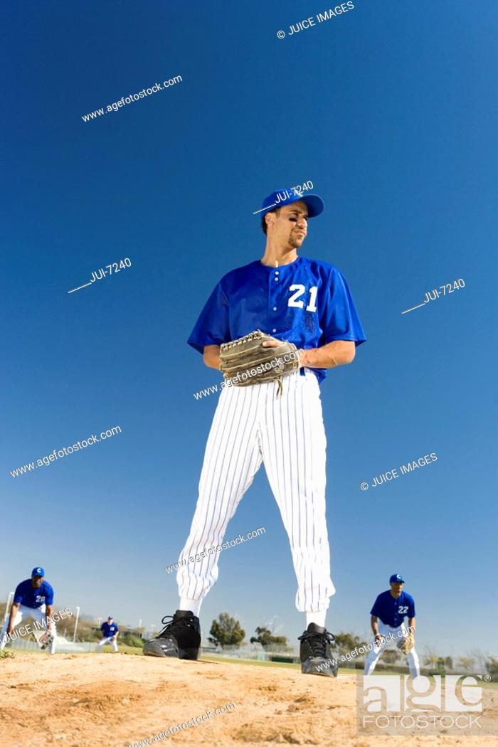 Stock Photo: Baseball pitcher, in blue uniform, preparing to throw ball during competitive game surface level, tilt.