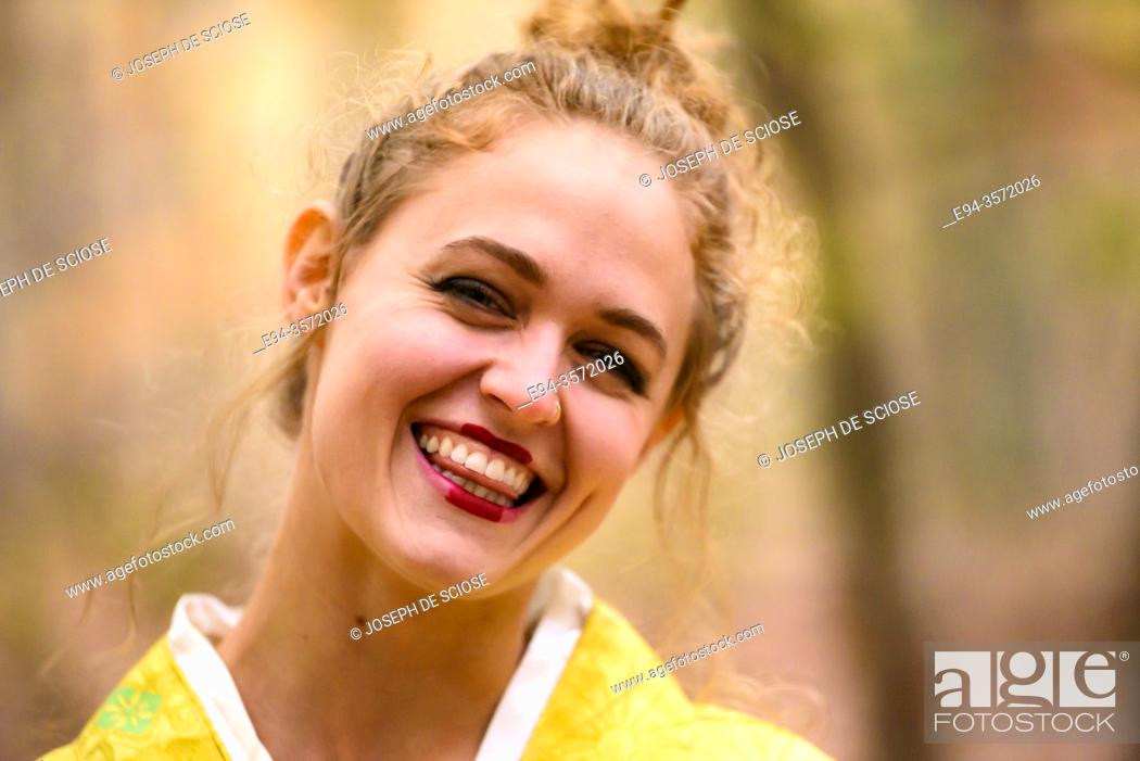 Stock Photo: A 28 year old blond woman dressed in a yellow kimono in a forest setting.