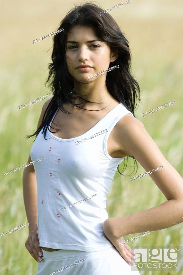Stock Photo: Young woman standing in field, looking at camera, portrait.