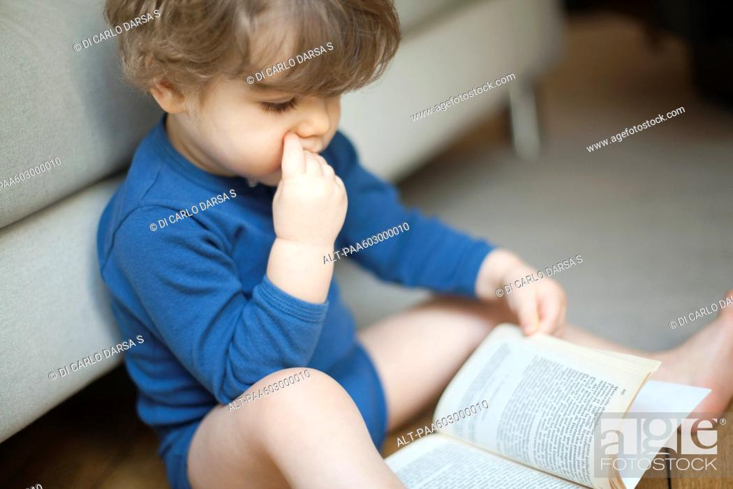 Stock Photo: Toddler boy looking at book.