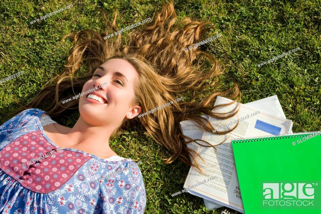 Stock Photo: High angle view of a young woman lying in a lawn.