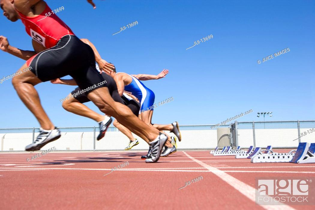 Stock Photo: Male sprinters leaving starting blocks, low angle view.