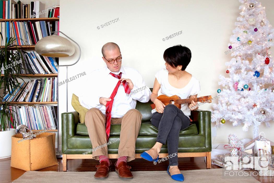 Imagen: Couple enjoying gifts near Christmas tree.