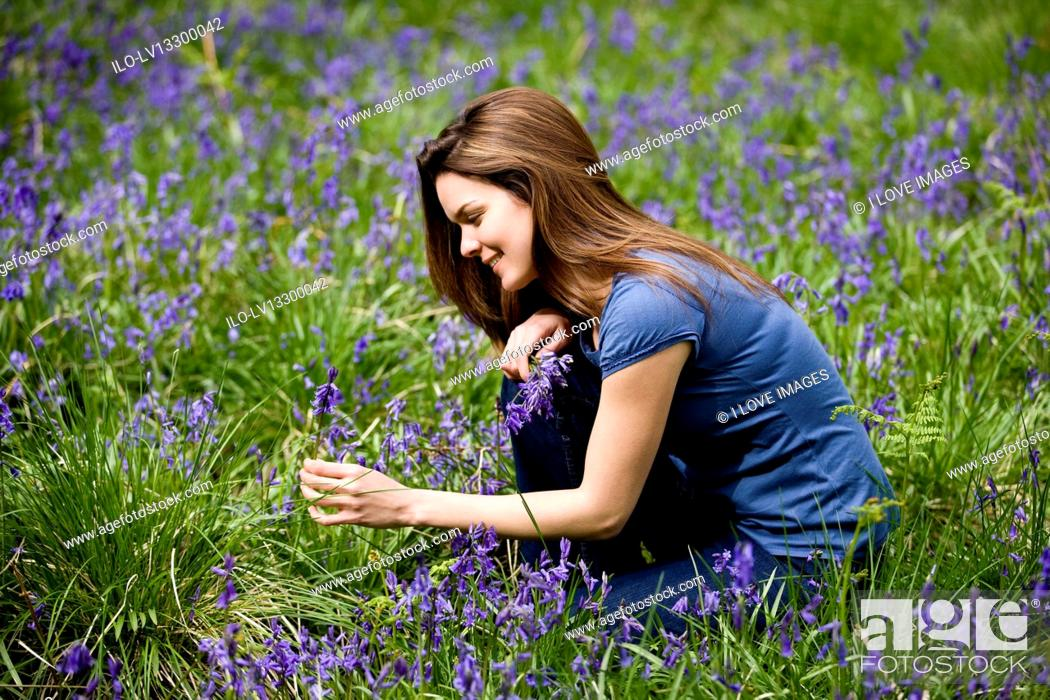 Stock Photo: A young woman picking bluebells, smiling.