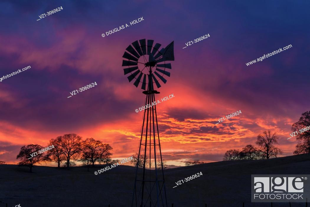 Stock Photo: Sunset storm clouds and colors form a backdrop for a foothill farm's windmill. Sierra Nevada Foothills, California, USA.