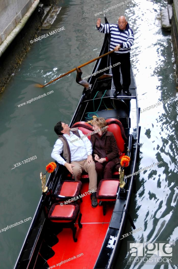 Stock Photo: Tourist taking a gondola ride in the water canals of Venice Italy.