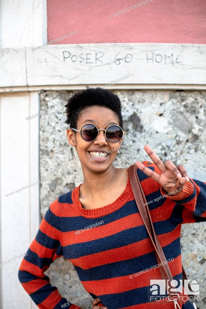 Photo de stock: Portrait of smiling young woman wearing sunglasses and striped pullover showing victory sign.