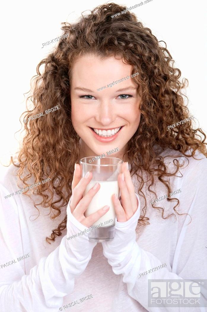 Stock Photo: Portrait of a woman holding a glass of milk and smiling.