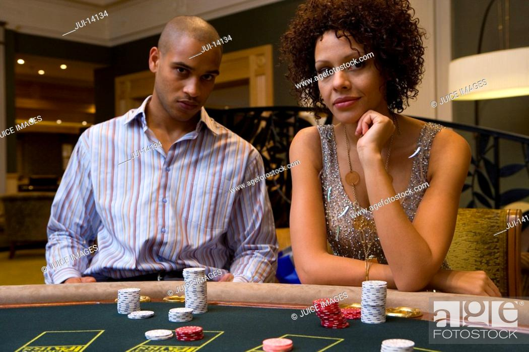 Stock Photo: Young man and woman gambling at poker table, portrait.