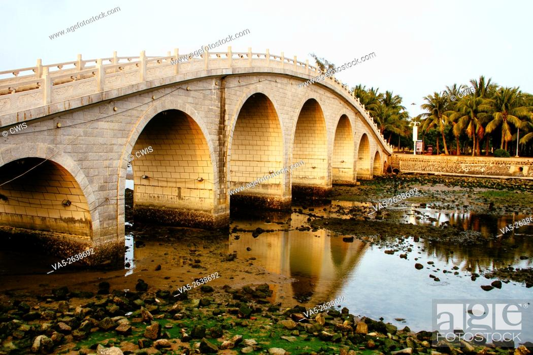 Imagen: Haikou, Hainan Island, China - The view of a stone arch bridge at sunset.