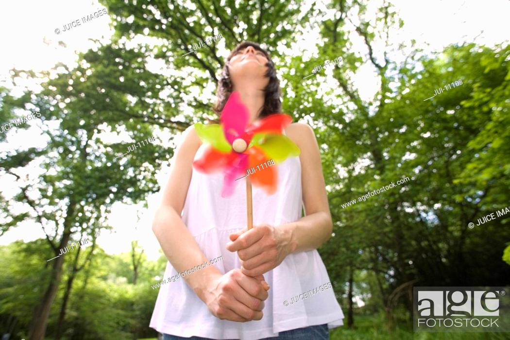 Stock Photo: Close-up of windmill held by 20's woman looking up at sky in leafy countryside,.