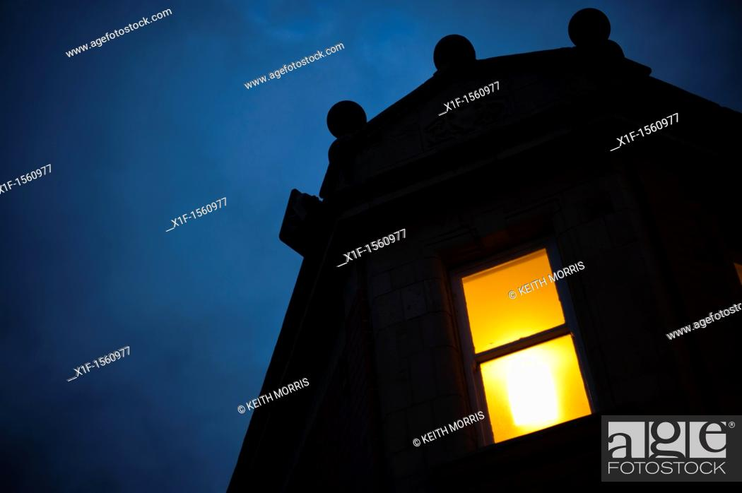 Stock Photo: A single illuminated window at night on the corner of a building.