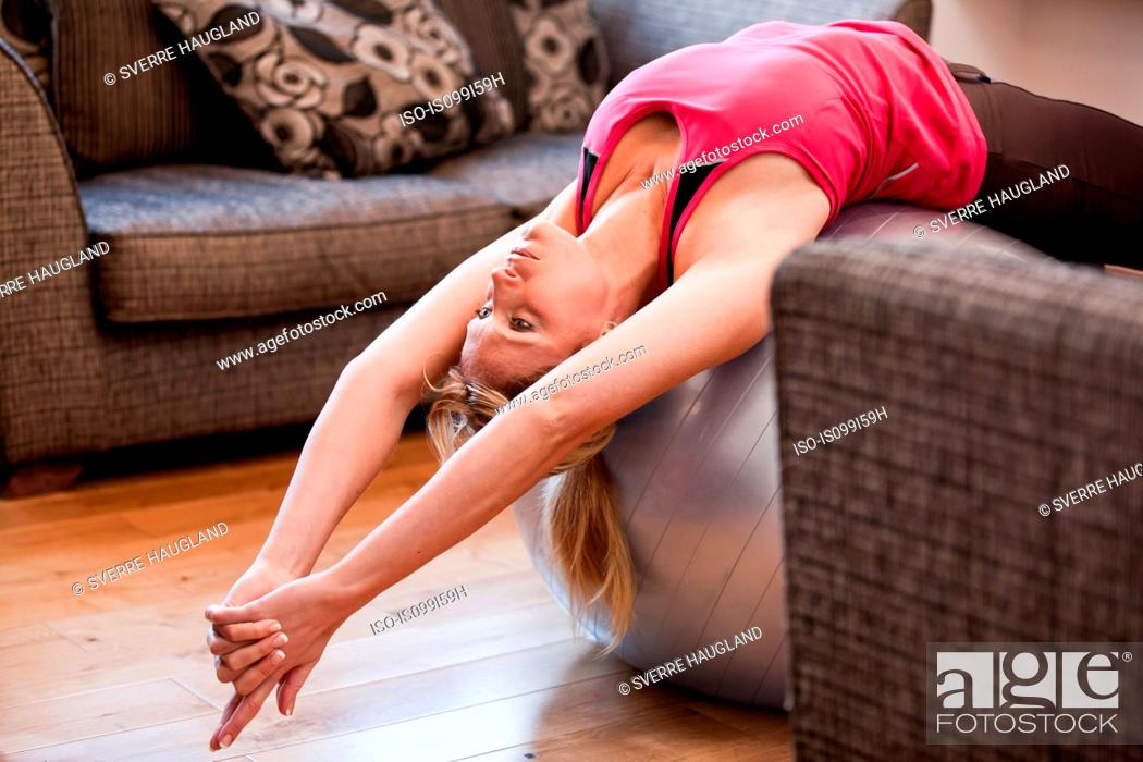 Stock Photo: Mid adult woman stretching on exercise ball at home.