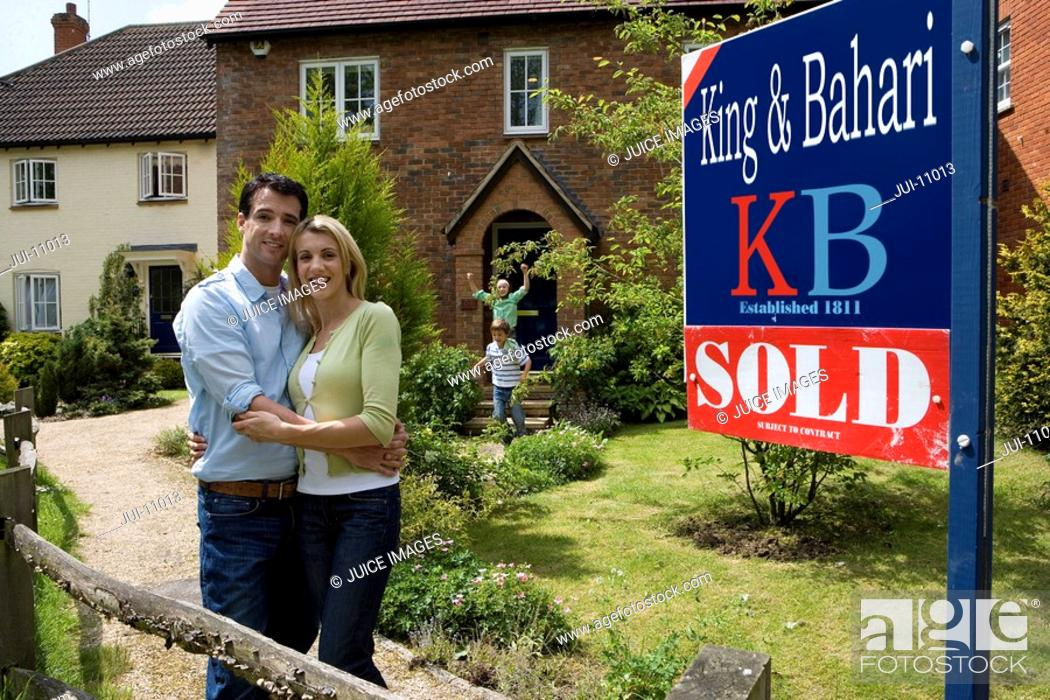 Stock Photo: Young couple embracing outside house with 'sold' sign, smiling, portrait.
