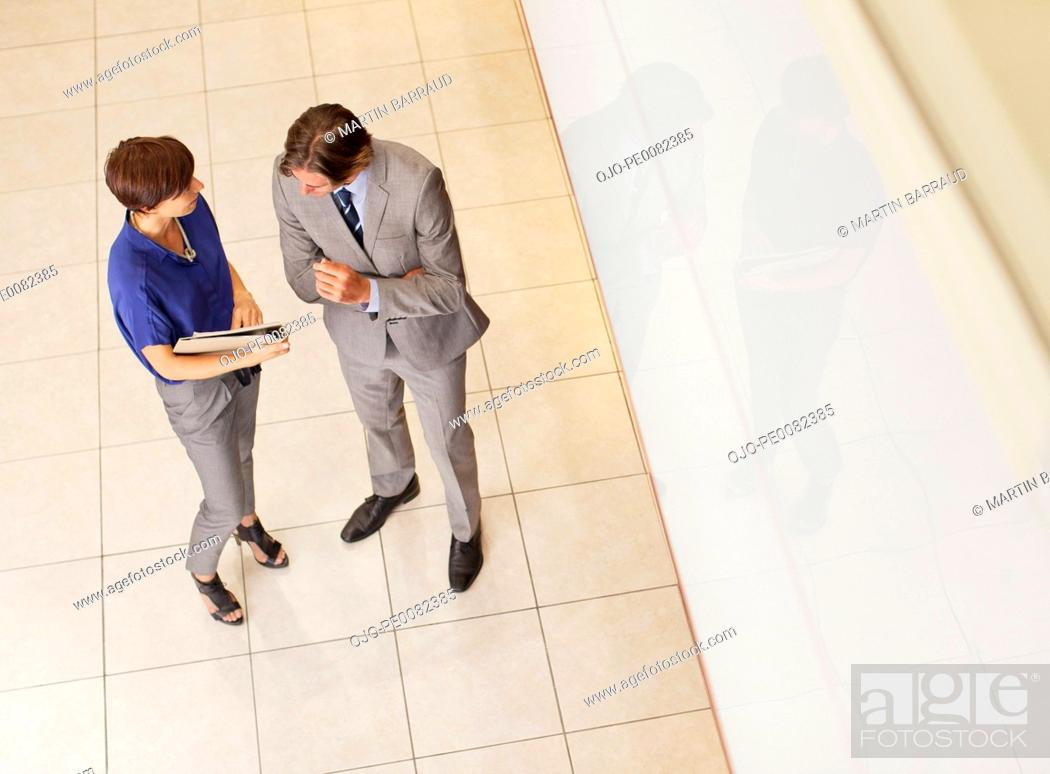 Stock Photo: Businessman and businesswoman reviewing paperwork in corridor.