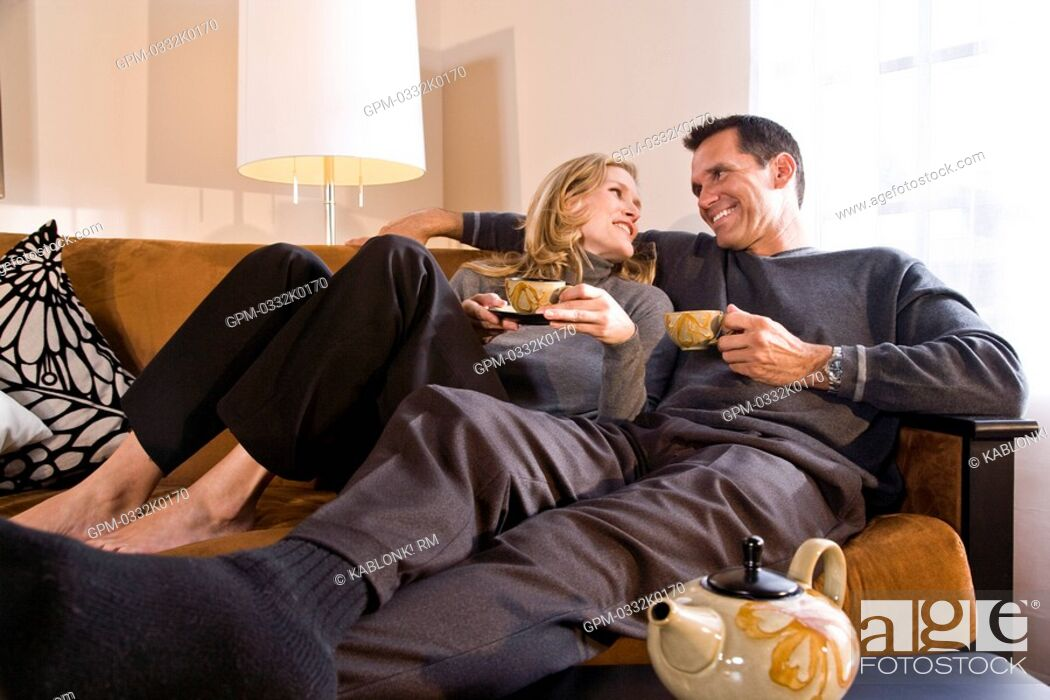 Imagen: Mid adult couple relaxing on sofa together drinking tea.