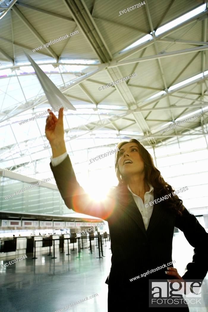 Stock Photo: Young businesswoman throwing paper airplane in airport.