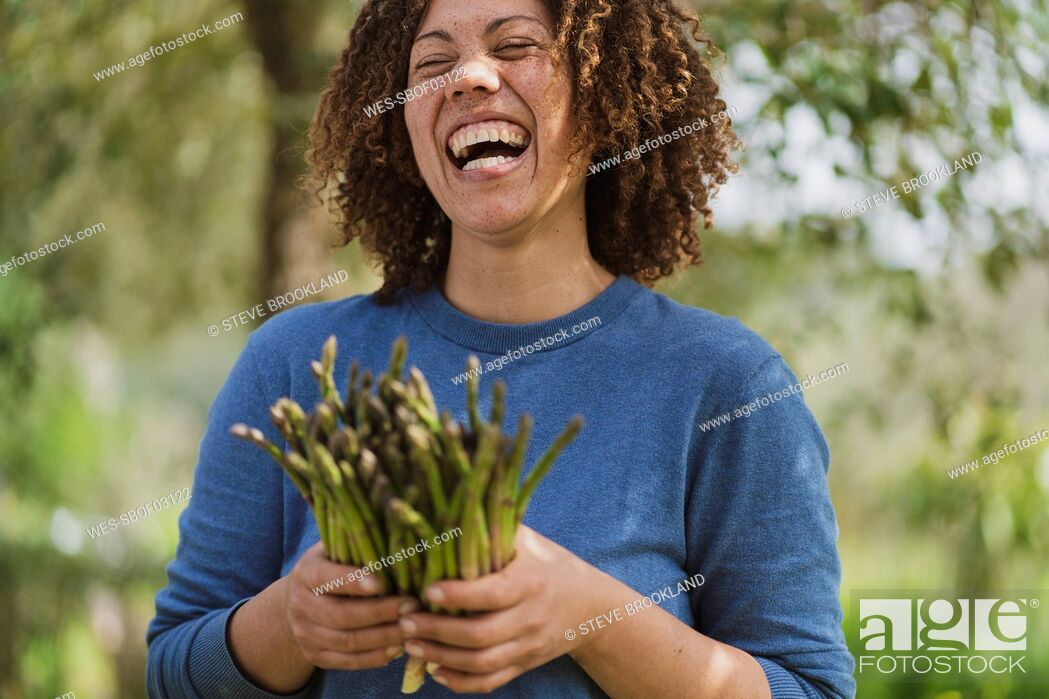 Stock Photo: Laughing woman holding fresh green asparagus in permaculture garden.