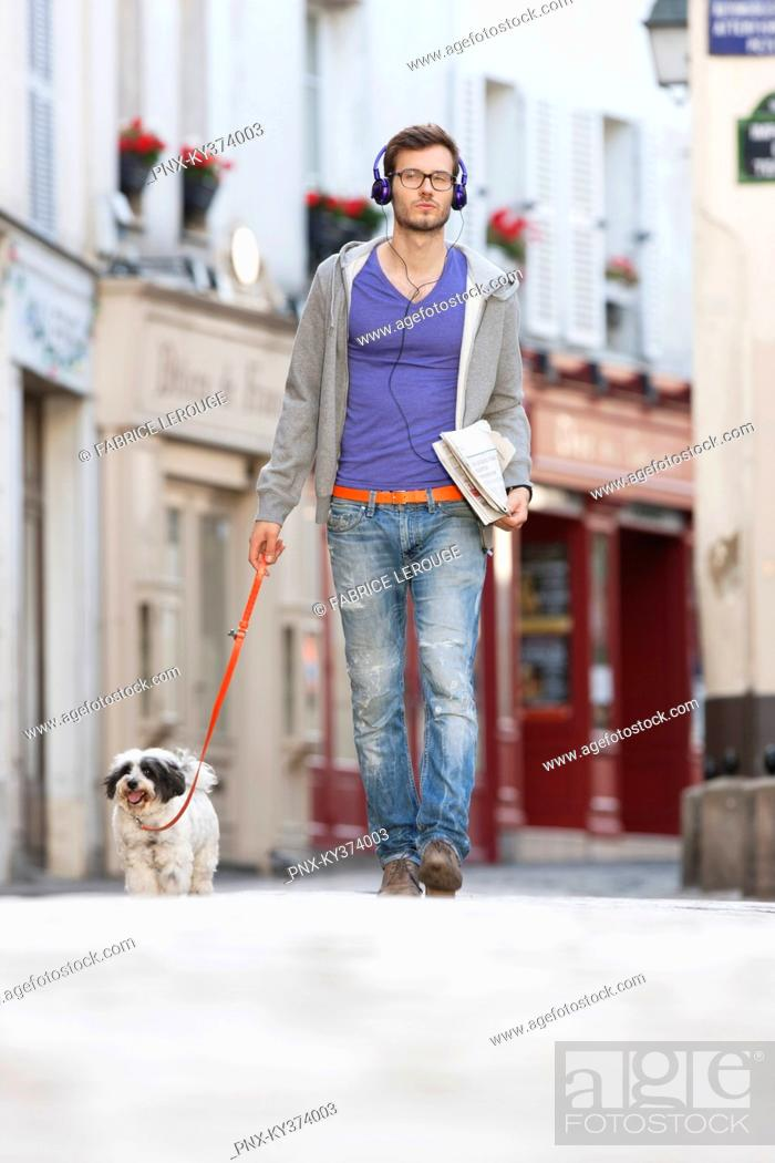 Stock Photo: Man holding a dog on leash, Paris, Ile-de-France, France.