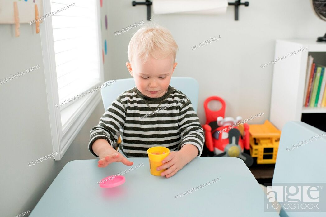 Stock Photo: Young boy sitting at table, opening tub of pink dough.