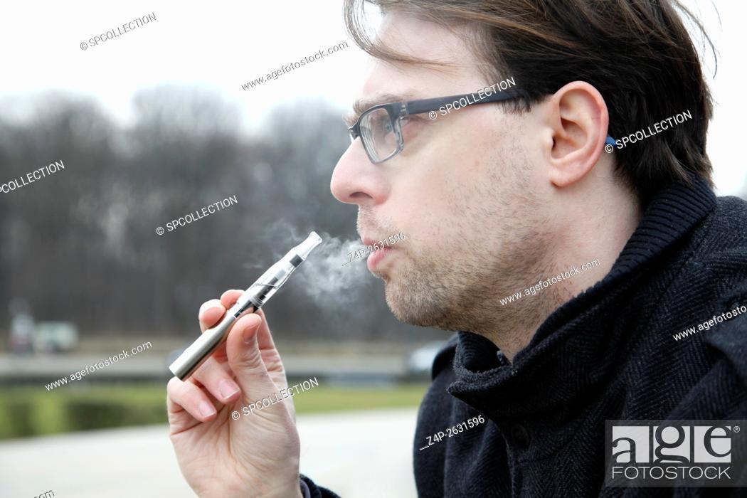 Stock Photo: Young man smoking an e-cigarette.