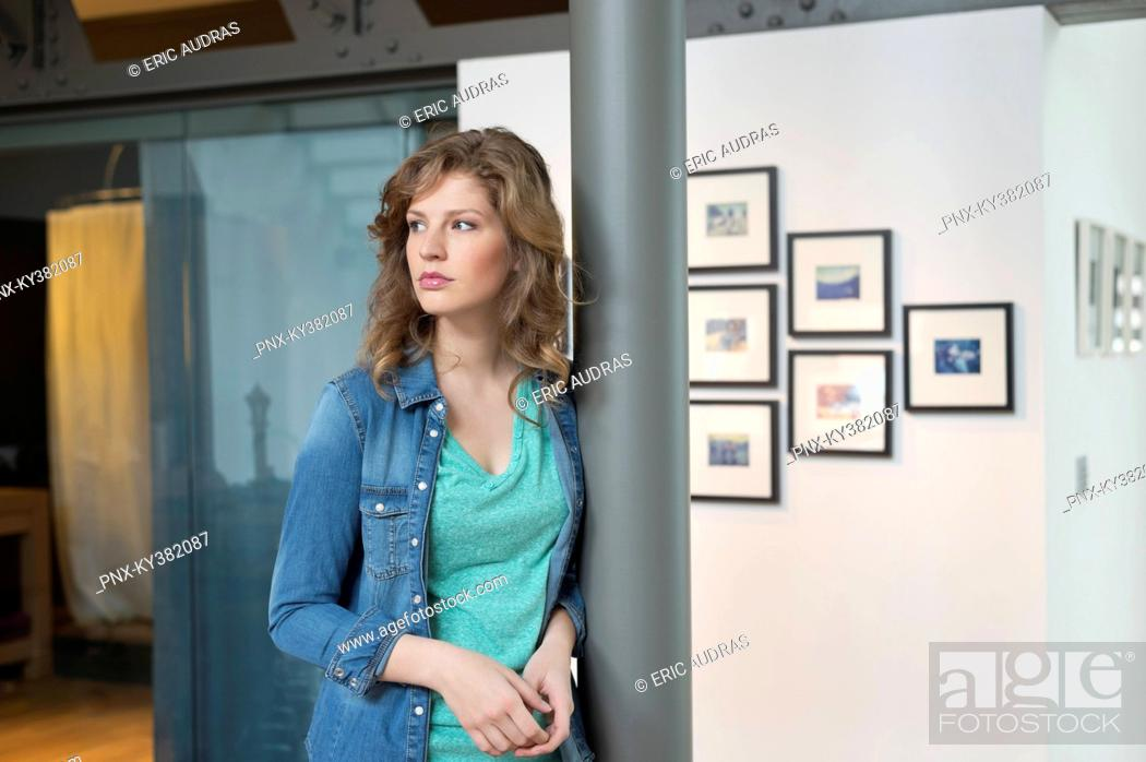 Stock Photo: Woman leaning against a column and thinking.