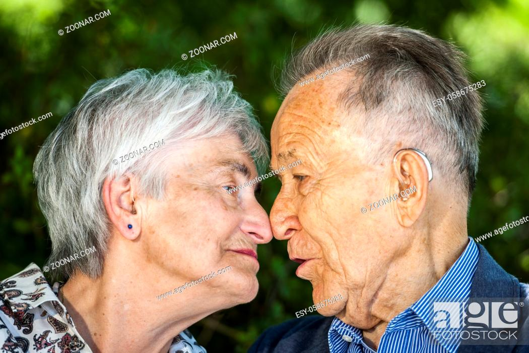 Stock Photo: Head-and-shoulder portrait of an elderly pensioner couple with glasses in front of green leaves in summer looking happily at the camera.
