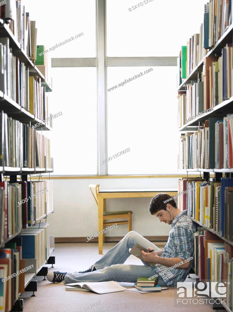 Stock Photo: Student reading sitting on floor in library.