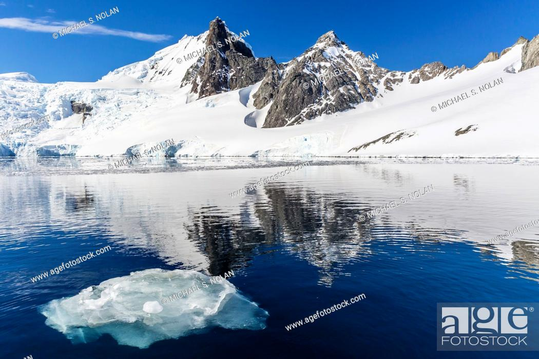 Imagen: Calm seas reflect snow-capped mountains, Orne Harbor, Antarctica.