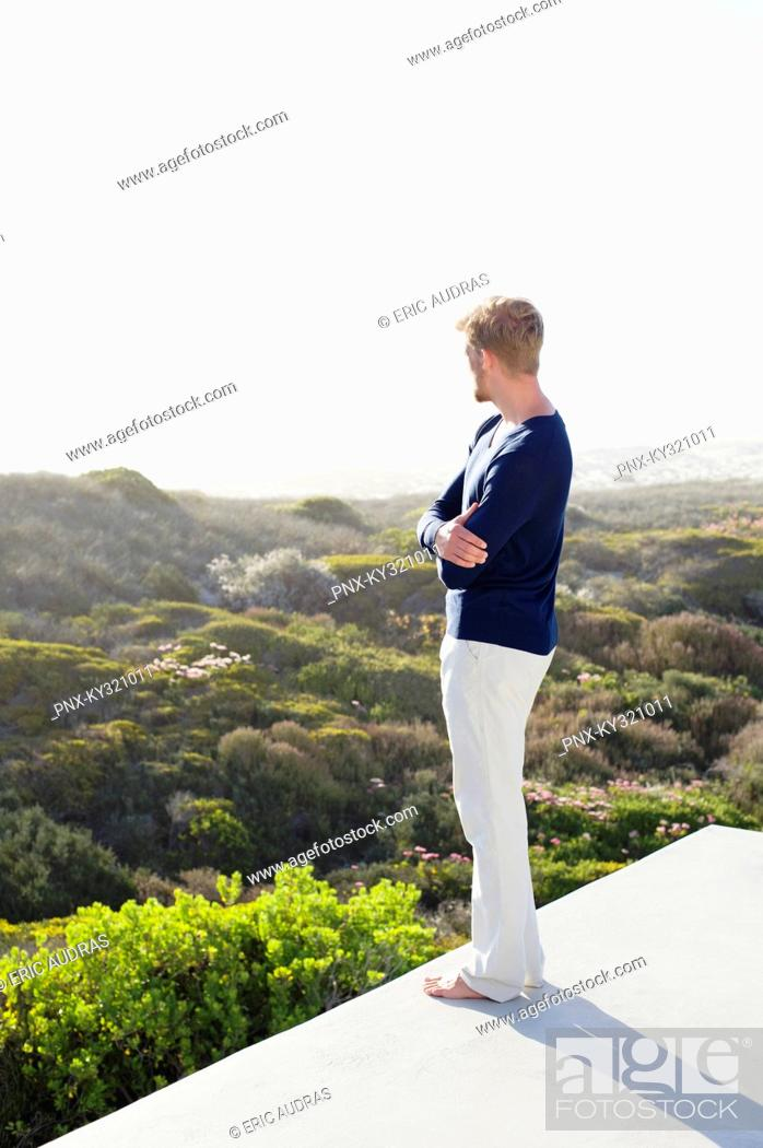 Stock Photo: Young man looking at view from the terrace of a house.