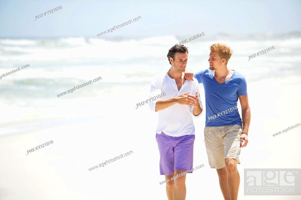 Stock Photo: Two men walking on the beach.