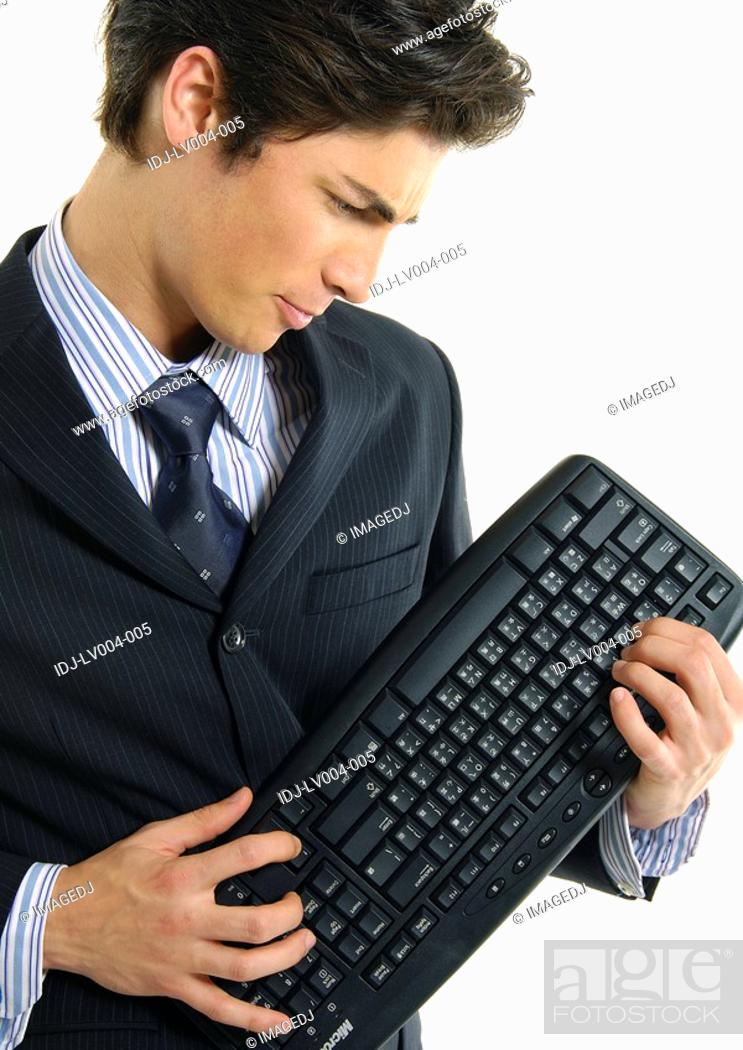 Stock Photo: Businessman holding a computer keyboard.