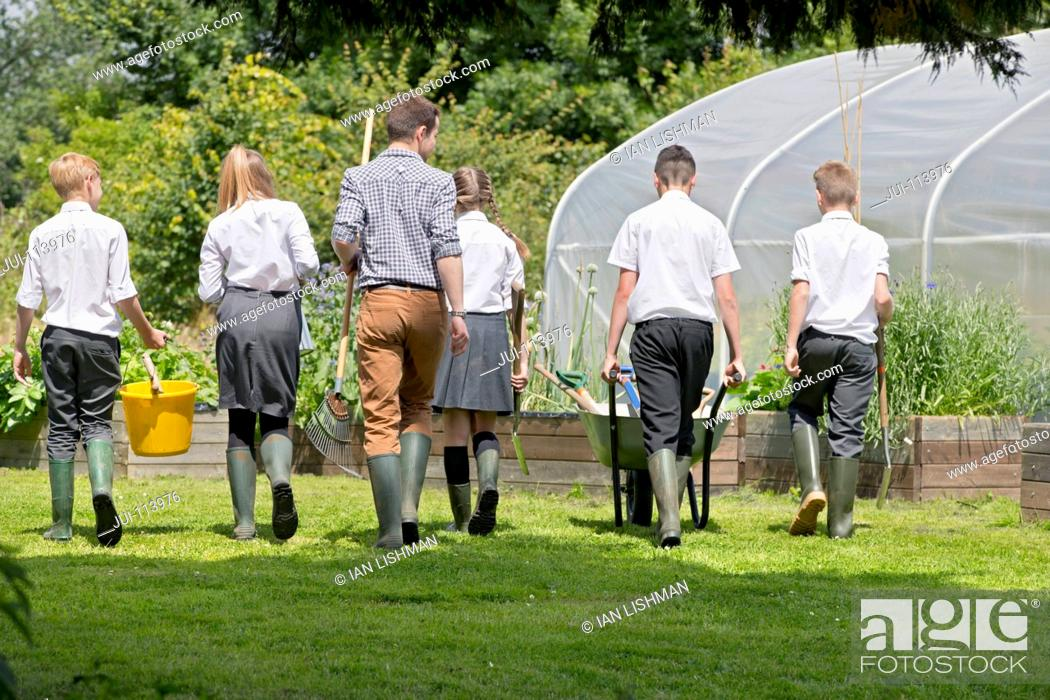 Stock Photo: Teacher and middle school students with wheelbarrow learning gardening in vegetable garden.