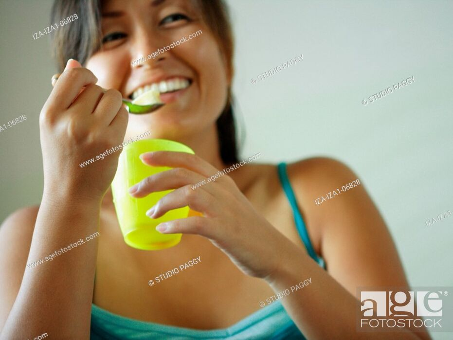 Imagen: Mid adult woman eating egg pudding and smiling.