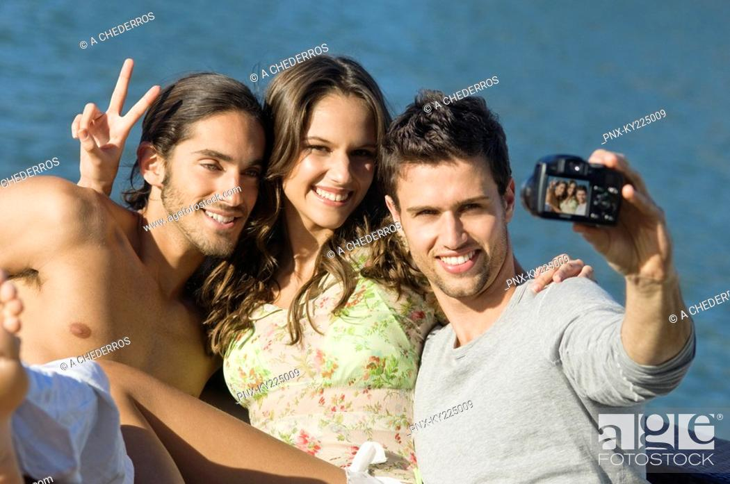 Stock Photo: Three friends taking a picture of themselves with a digital camera.