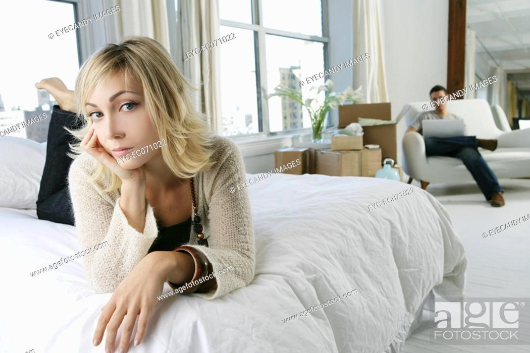 Stock Photo: Young woman laying on bed with man behind.