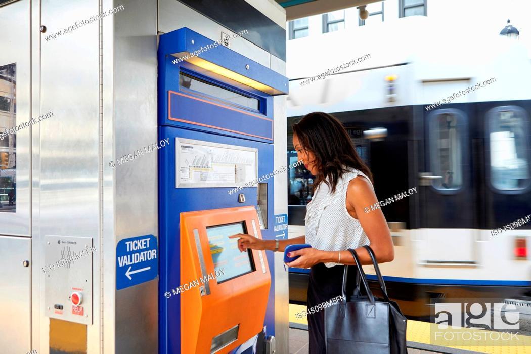 Stock Photo: Businesswoman buying train ticket at machine.