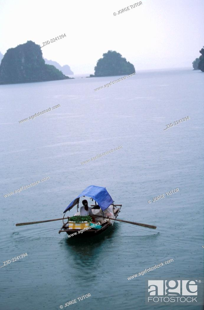 Imagen: Woman vendor rowing a boat in a rainy day H? Long Halong BayUNESCO World Heritage Site Vietnam.