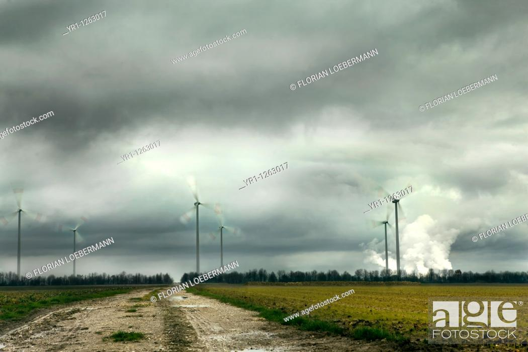 Stock Photo: Windpark in North Rhine-Westphalia, Germany with a lignite-fired power plant in the background. Long exposure with motion blurred blades.