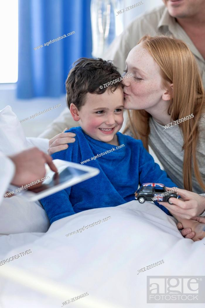 Imagen: Family and doctor visiting little boy lying in hospital bed.