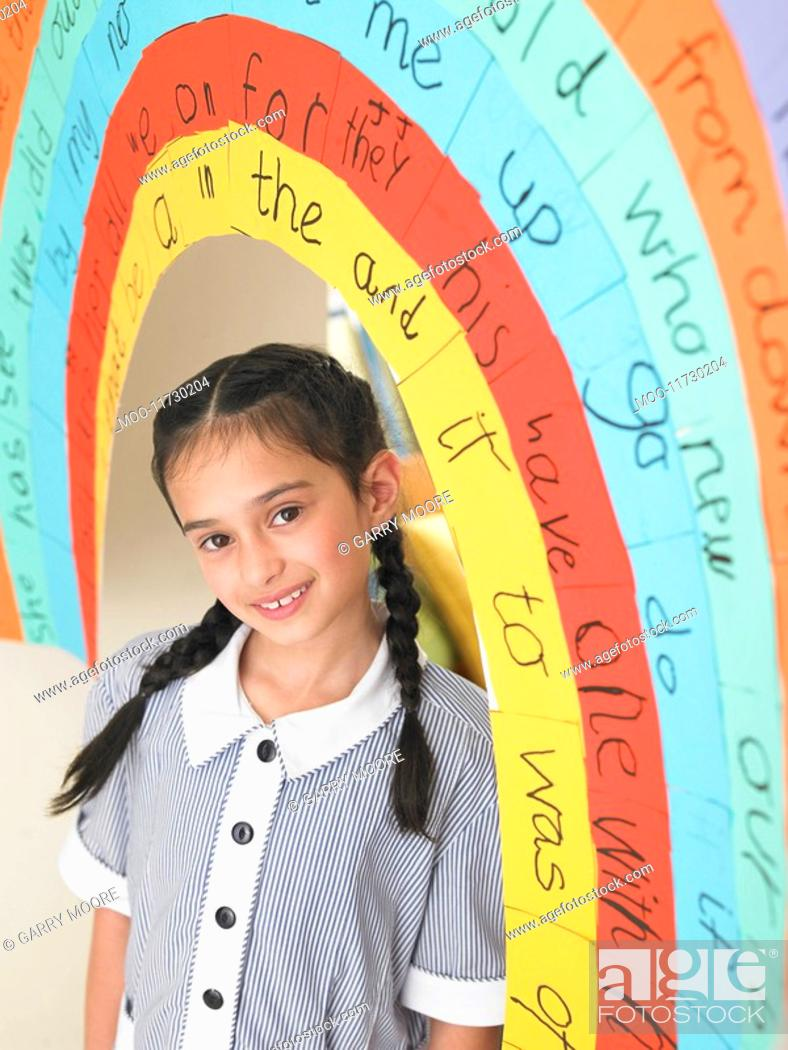 Stock Photo: Elementary schoolgirl standing under painted arch in classroom portrait.