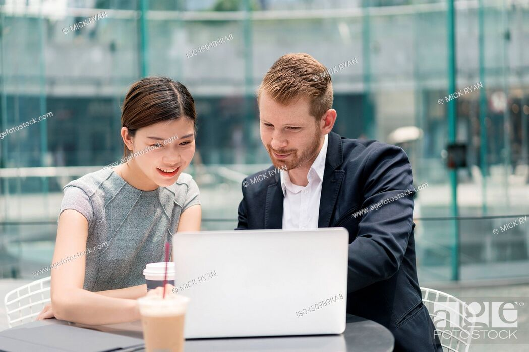 Stock Photo: Young businessman and woman looking at laptop at sidewalk cafe meeting.