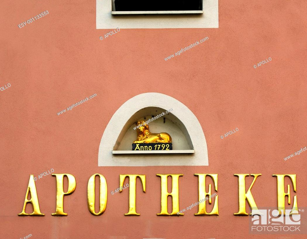 Stock Photo: Lion sculpture above a gilded script Apotheke or pharmacy, Germany.
