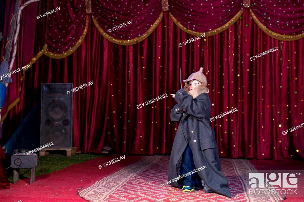 Stock Photo: Young Boy Wearing Clown Make Up, Hat and Over Sized Coat and Holding Sword on Stage with Red Curtain.