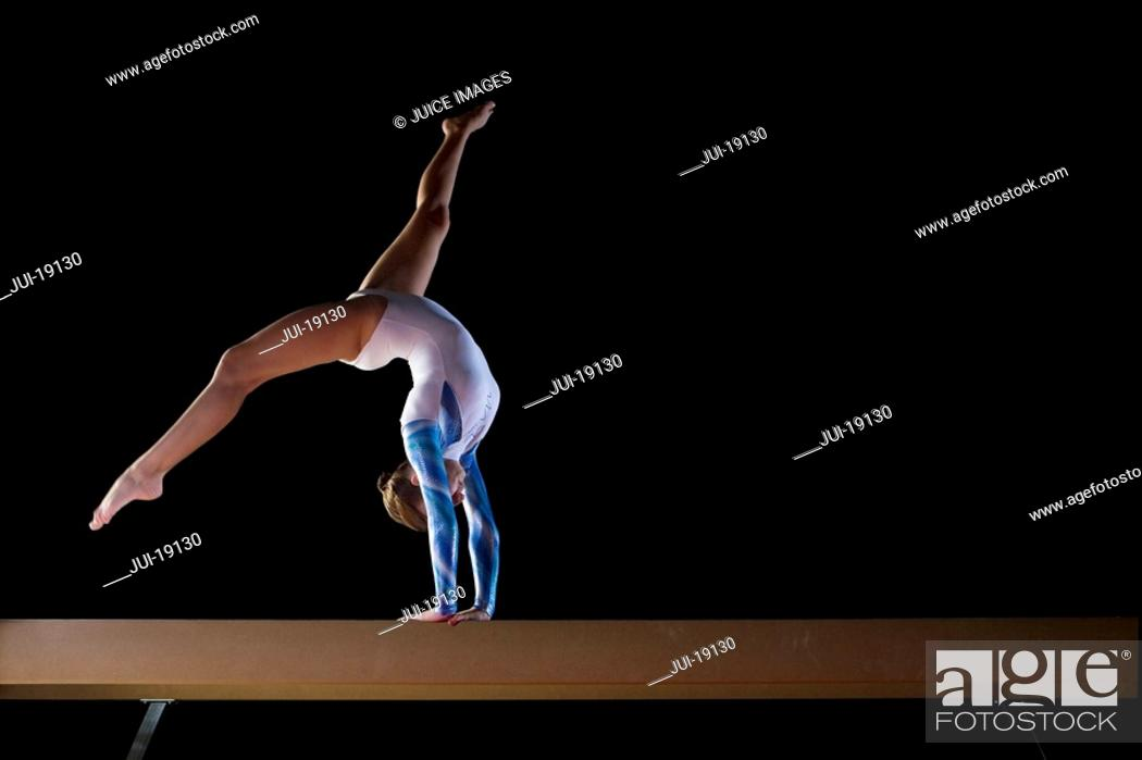 Stock Photo: Female gymnast performing on balance beam, low angle view.