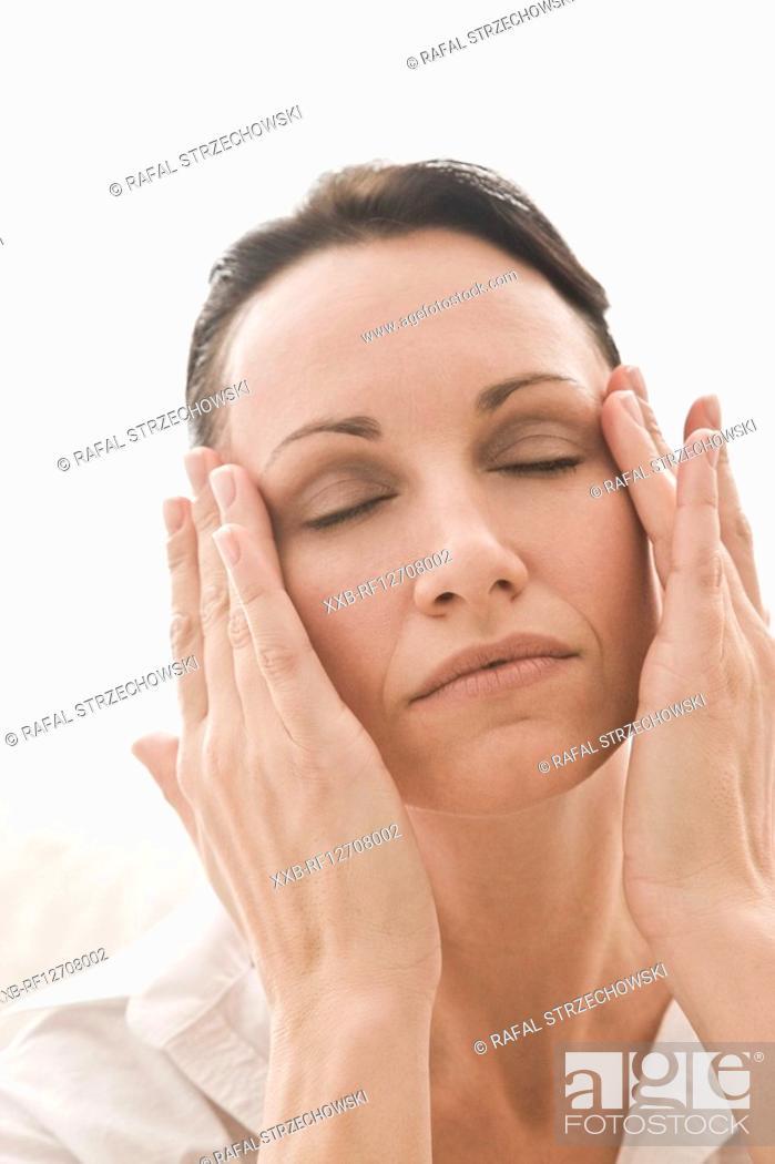 Stock Photo: woman massaging face.