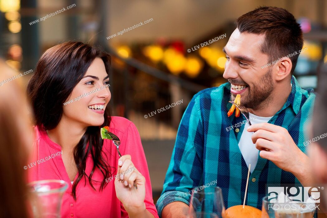Stock Photo: leisure, food and drinks, people and holidays concept - happy couple with friends having dinner at restaurant.